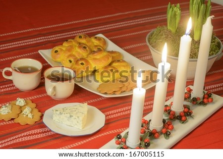 Swedish advent celebration Lucia buns and ginger bread on plate, blue cheese and mulled wine or glogg. Focus on plate - stock photo