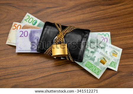 Swedish banknotes in a black wallet locked with a golden chain and padlock on wooden table. These are some of the new banknotes that were introduced in Sweden year 2015. - stock photo