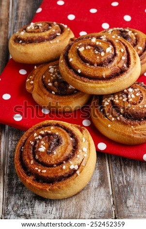 Swedish cinnamon buns on red dotted fabric - stock photo