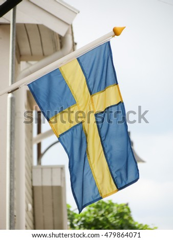 Swedish flag floating from a wooden building