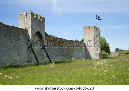 Swedish flag on top of a medieval wall on Gotland island. - stock photo