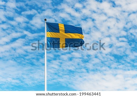Swedish flag waving in wind against a blue sky with light white clouds, horizontal - stock photo