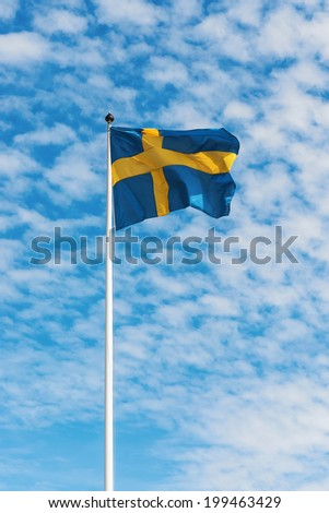 Swedish flag waving in wind against a blue sky with light white clouds, vertical - stock photo