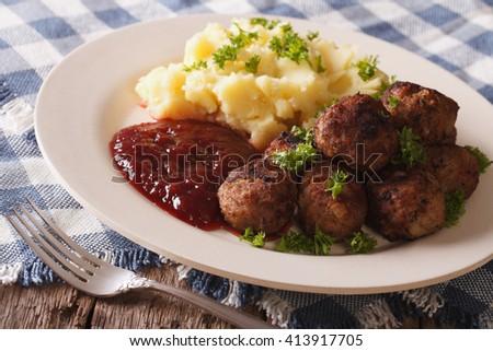 Swedish food: meatballs, lingonberry sauce with potato garnish on a plate close-up. horizontal - stock photo