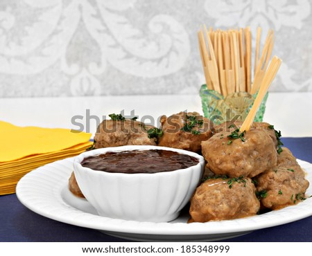 Swedish meatballs, stacked with a side of berry sauce.  Toothpicks and napkins for the appetizer.  Copy space. - stock photo