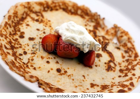 Swedish pancake with whipped cream and strawberries on a white plate - stock photo