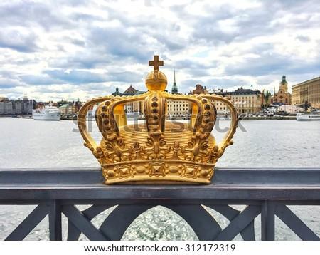 Swedish royal crown on a bridge, view over Gamla Stan. Stockholm, Sweden. - stock photo