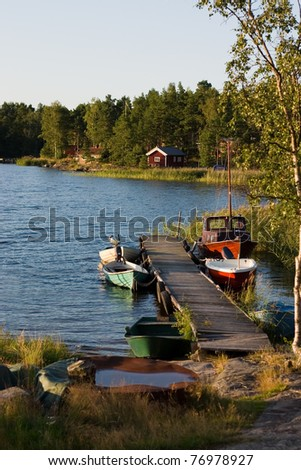 Swedish summer place , red house , boats in the lake - stock photo