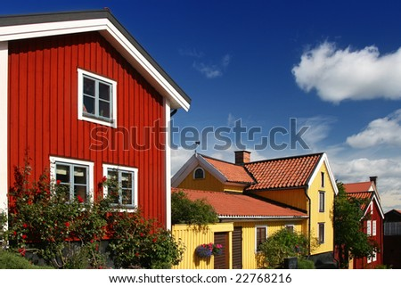 Swedish wood houses in red and yellow with blue sky - stock photo