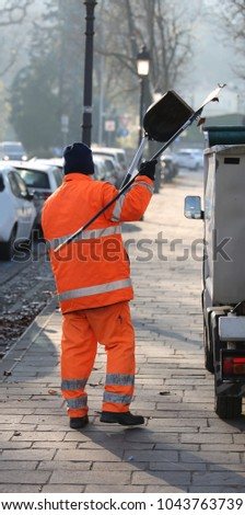 sweeper with an orange jacket collecting rubbish along the streets of a big city