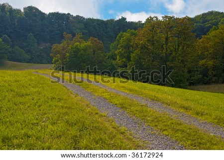 sweeping country farm road in West Virginia hills.