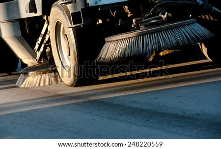 Sweeping machine cleans the street closeup. - stock photo