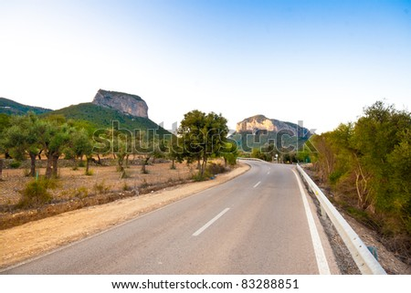 Sweeping road under the mountains - stock photo