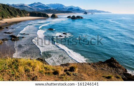 Sweeping view of the Oregon coast, miles of white sandy beaches, sea stacks and ocean waves. Location: Cliff's edge at Ecola Park overlook in the Pacific Northwest, USA - stock photo