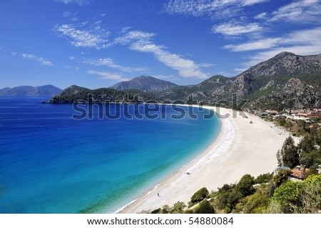 Sweeping white beach with blue sky and sea - stock photo