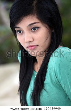 Sweet adorable asian woman in green t-shirt smiling - stock photo