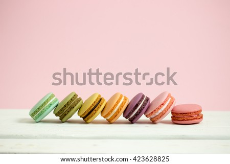 Sweet and colorful french macaroons or macaron on white wooden table pink background, Dessert. - stock photo
