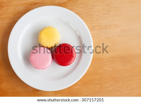 Sweet and colourful french macarons on wood background