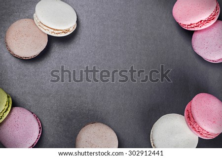 Sweet and colourful french macaroons on a black background. focus on the black background. Background can be used for text - stock photo