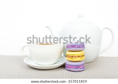 Sweet and colourful french macaroons with tea cup and teapot