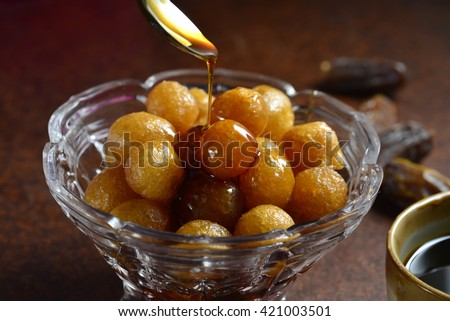 Sweet and natural date syrup is being poured on deep fried dumplings - Luqaimat. Arabic home made sweet delicacy. - stock photo