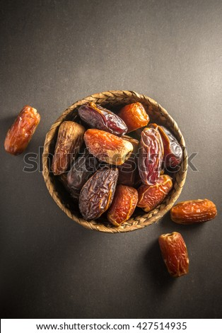 Sweet and ripen dates in basket. Most common and popular fruit in Arabian countries. Top view on dark background.  - stock photo