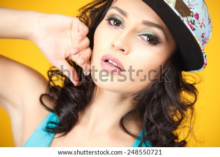 Sweet and sexy brunette young woman in sport style over yellow background