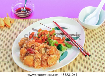 Sweet and Sour Chicken Dinner in Chinese Restaurant setting on bamboo place mat.  Purple background with copy space.