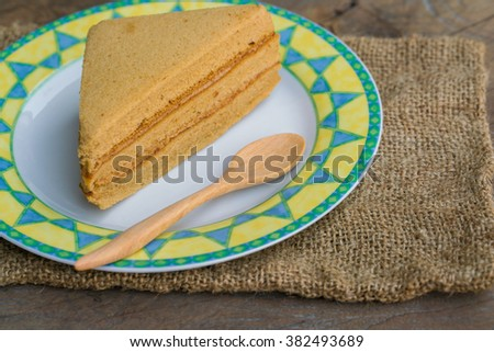 Sweet and tasty Coffee flavoured cake in dish and wooden spoon.  great for during coffee break. - stock photo