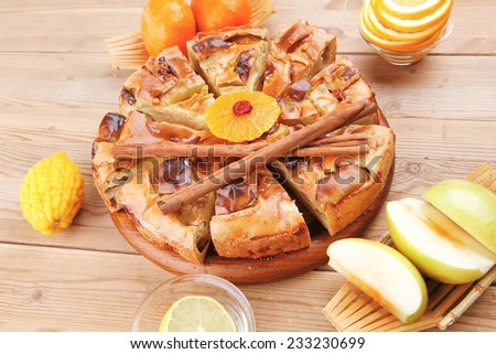 sweet apple pie cuts served with apples lemon mandarin and tea cup on wooden plate over table - stock photo