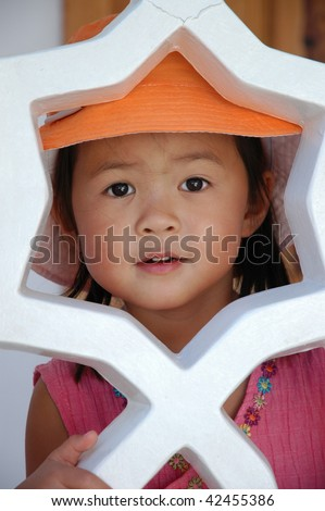 sweet asian girl sitting on the stairs looking through a star shaped railing - stock photo