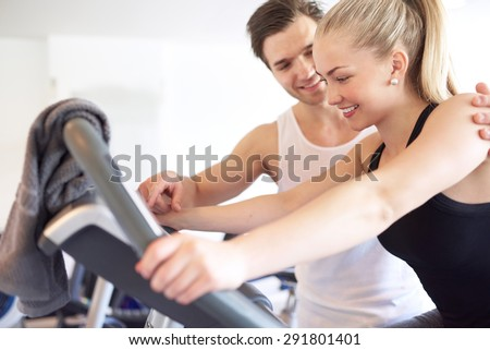 Sweet Athletic Handsome Boyfriend Assisting his Pretty Girlfriend Doing an Exercise on Elliptical Bike Inside the Gym