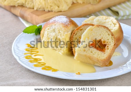 Sweet Austrian yeast pastry dumplings stuffed with apricot jam and served with vanilla sauce