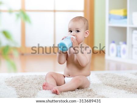 sweet baby boy holding bottle and drinking milk - stock photo