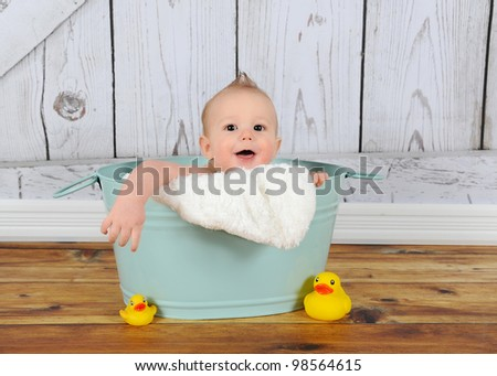 sweet baby boy playing peek-a-boo in washtub - stock photo