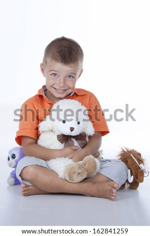 sweet baby boy posing for the camera with her soft toys