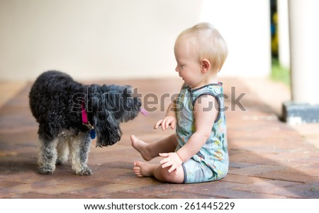 Sweet baby boy sitting with his pet dog who is about to lick him - stock photo