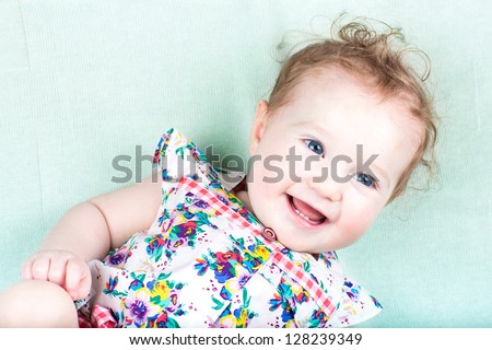 Sweet baby girl in a summer dress on a green knitted blanket - stock photo