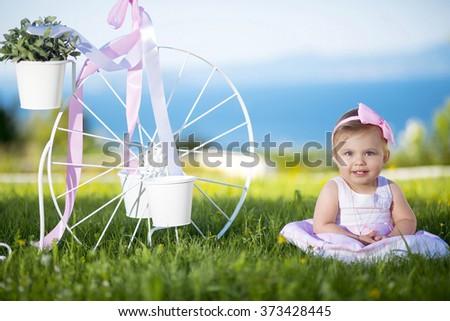 Sweet baby girl playing  outdoors   - stock photo