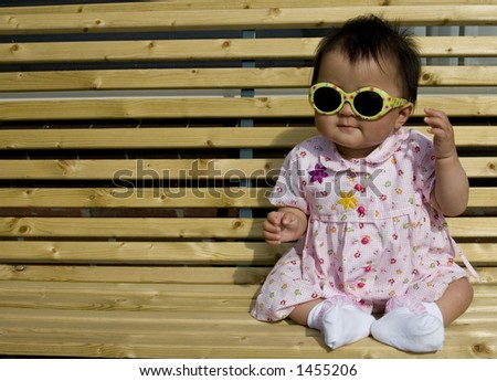 sweet baby girl sitting on a the porch wearing sunglasses - stock photo