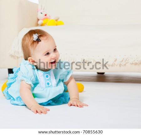 Sweet baby girl sitting on the floor - stock photo