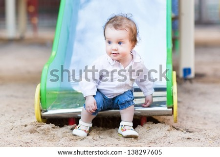 Sweet baby girl with beautiful blue eyes playing on a slide - stock photo