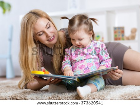 sweet baby girl with mother reading book in nursery - stock photo