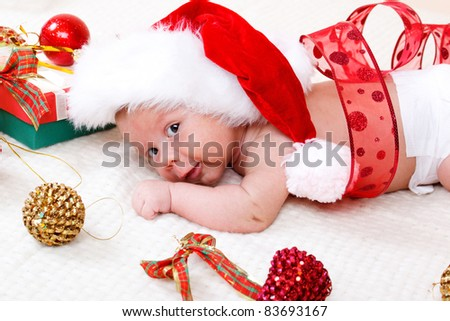 Sweet baby in Christmas hat decorated with red ribbon - stock photo