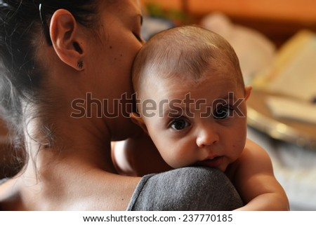 sweet baby in mother's arm smile - stock photo