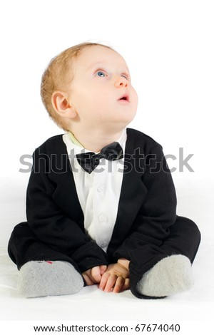 sweet baby in tailcoat sitting on white ground - stock photo