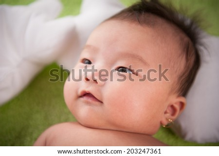 Sweet baby infant close-up portrait on a green blanket - stock photo