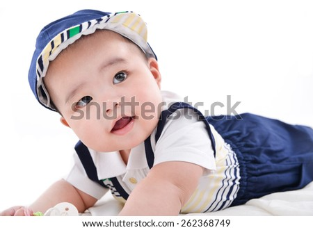 sweet baby laying with hat on the bed