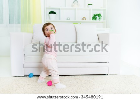 Sweet baby little girl standing in front of the sofa, holding baby toy.Living room interior.Shallow doff, copy space - stock photo