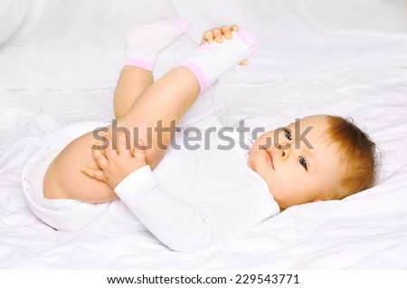 Sweet baby lying in bed at home - stock photo